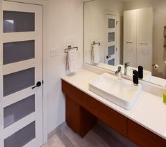 The starting point and inspiration began with this sleek, Scandinavian designed bathroom vanity. Serenissima Travertini Grigio porcelain tile was chosen as it provides the ease of porcelain, yet the look of elegant natural stone. The basket weave pattern in the shower creates movement and interest. The simplicity of the sink, counter top and open glass shower lends a clean, contemporary feel. Of course...the frosted glass panelled door is just perfect!