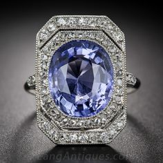 Belle Epoque romance, radiance and refinement coalesce in this extraordinary French made adornment - circa 1900. A bright and beautiful lavender hued blue sapphire, weighing 7.00 carats, glistens day and night from within a delicate double-tiered platinum frame glittering with old mine single-cut and rose-cut diamonds. Two pair of diamonds also twinkle atop the ring shank of this truly enchanting and feminine antique jewel. 13/16 inch by 9/16 inch; French eagle's head on outer...