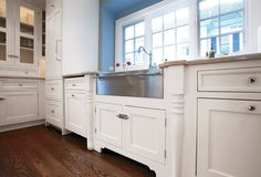 Painted white shaker kitchen cabinet with stainless knob pulls and stainless farm sink photo