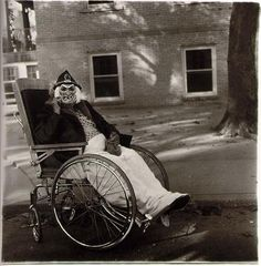 Masked woman in a wheelchair by Diane Arbus