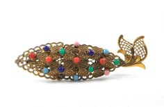 This abstract brass filigree fish brooch  is filigree brass with colorful glass beads  measures 3 1/4 by 1  has a clasp which works well  is