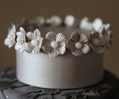 A tiny silver top tier is edged in flowers and pearls.