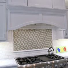 white kitchen cabinets with walker zanger tile backsplash and gas stove