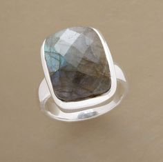 Like dappled light on the wide-open sea, a checker-cut labradorite shines on a sterling band. Imported. Whole sizes 6 to 9.