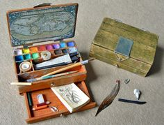 Schilderskistje met veer, potloden, waterverf, penselen en mooie afbeelding