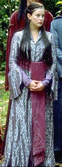 Arwen's Rivendell Farewell Gown: The fabric looks thin to me, like a silk with metallic flowers. It has a rolled collar and a V-neck, much like the Chase costume. The split open sleeves show a tighter plain purple undersleeve. THere is silver trim couched on the front to make a pattern. There are buttons down the front to the waist. The skirt is split in front, showing a purple underskirt. There is a sash with a front tail that goes to the floor with a silver pattern on it as well.
