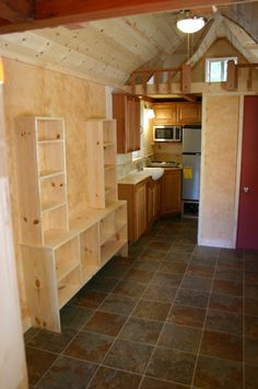 There is a built-in entertainment center in the tiny house living room and shelving in the kitchen.