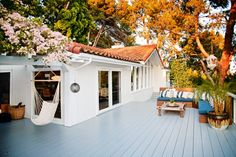 """At home with Miranda Kerr: The redwood deck wraps around the entire west side of the house. """"The space allows me to have an outdoor living area,"""" says Kerr, """"which is a must for me because I love being out in nature."""" The Indonesian teak daybed in the background is from Berbere World Imports; the hammock is a gift from a friend: """"It's where Flynn and I like to curl up and watch the sun set over the ocean."""""""