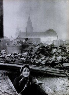 A girl emerges from a bomb shelter surrounded by the ruins of Nagasaki, 1945.