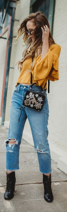 Edgy spring outfit styled with mustard ruffled sweater, Levi jeans, black booties, and embellished crossbody #springoutfit #weekendoutfit #blackboots