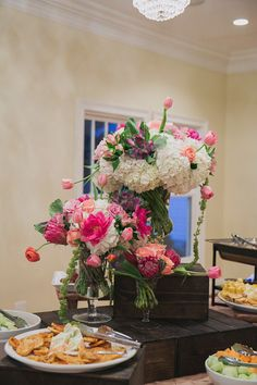 In-house florist, Corey Hults, created this fun food table centerpiece using bright and cheerful blooms from the wedding palette. | The Sonnet House | Photo by Jett Walker Photography