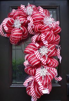 Deco Mesh Candy Cane Wreath, Christmas Mesh Wreaths, Christmas Wreath, Candy Cane Decoration    Ready to ship! XXL candy cane    Festive candy cane deco mesh wreath! This is a statement piece. Filled with pretty mesh, candy cane stripe ribbon, & snowflakes. Perfect for your door or favorite wall. Red & white makes everything nice!    38 Tall by 25 Wide by 8.5 Deep  Measurements are approximate but very close.    The poly mesh is weather friendly, but the ribbon will last longer if place in a…