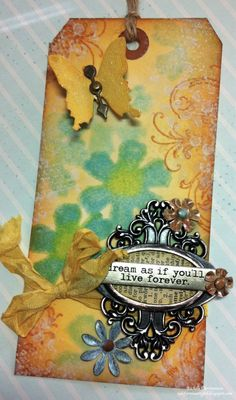 Another great tag background from Richele Christensen.  She made a custom foam stamp and used distress stains for the first layer (there are shadow stamps of the foam stamp image that help create this dimensional look).  She stamped the flourish with distress in and grunge overlay on top of that.  Then embellishments are added.  At californiagirlblogspot.com