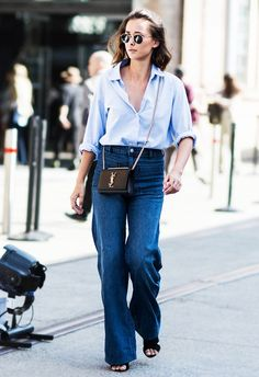 A blue button-down blouse is paired with high-waisted denim flares, a YSL bag, and black sandals