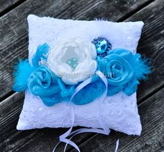 This exquisite 'Touch of Elegance by Del' ring bearer pillow is made with white shantung silk and Alencon lace overlay (hand sewn beaded)! A gorgeous peony flower and teal / tiffany blue roses adorn the pillow. A stunning sparkling tiffany blue rhinestone jewel accentuates the beauty of your pillow, bringing in that wow factor that you were looking for, making your wedding pillow unique and sophisticated!  #timelesstreasure