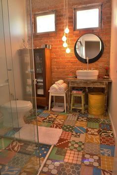 #reforma #baño con lavabo blanco de diseño sobre mesa restaurada, espejo circular, cabina de ducha con cerramiento de vidrio, suelo baldosas hidráulicas