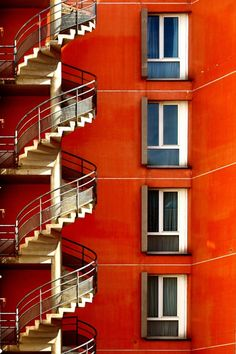 I like the curviness of the stairs contrasted with the straight lines of the windows and walls. Photo by Eric Foley. Fire Escape, Take The Stairs, Stair Steps, Red Walls, Stairway To Heaven, Interior Exterior, Architectural Elements, Beautiful Buildings, Architecture Details