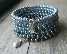 This 6 coil bracelet is made with stainless steel memory wire - will adjust to the size of your wrist and no chance of breaking. This will ensure you will have this bracelet for a long time. Materials include 4mm glass seed beads in colors of blue denim. Accented with dainty Tibetan silver spacer beads. Finished off with small silver swirl charms on each end.  This bracelet is on the lighter side in weight.  Thrifty Thursday Item 7/7/16 Original Price $19.95 TT Price $11.95 + free shipping