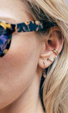 Stacked earrings and tortoise shell glasses.