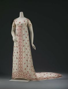 "Formal gown, French, 1800-1805. ""White cotton gauze on which is a powdering of small floral sprays and a border design composed of vine and a modified Greek fret worked in a chain stitch with fine red and white wool."" MFA Boston 22.665"