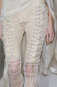 Leave the waist band intact. Cut straight strips, poke holes and lace up. This would make those tiny pants fit your not so tiny rear end.