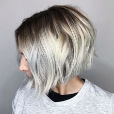 side view of woman with short angled bob with waves on ash hair