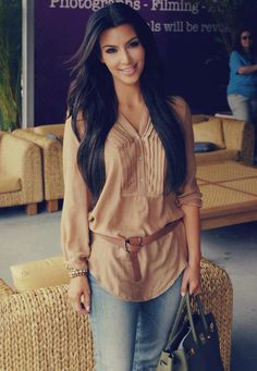 Kim Kardashian sporting a laid back look, brown blouse and belt, dirtied jeans, and a hunter green purse.