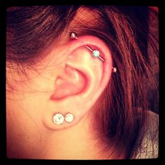 Industrial piercing with two earlobe piercings.