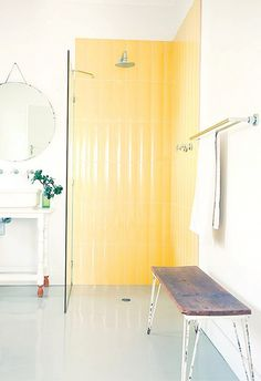 Yellow is such a bright and cheerful color and the yellow tile in this bathroom really sets the shower apart from the rest of the all-white bathroom.  I'm a huge fan of the wet room style shower too.