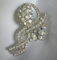 Lovely silver tone metal brooch with faceted navette cut and round cut rhinestones. Measures 2 1/4 long. This piece is in very good preowned