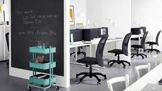 Kantoorhotel ingericht met zwarte bureaustoelen en zwarte schermen tussen witte bureaus
