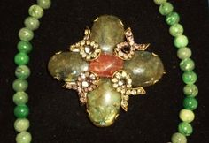 """The pin in the middle is an original Iradj Moini his jewelry has been exhibited at """"The Metropolitan Museum of Art"""" and the """"Louvre"""". Necklace is polished green stone.http://www.theguildshop.org/irad-moini/ Pin: $878.40 semi precious stones Necklace: $144.00 S0126 01 02/26/15"""