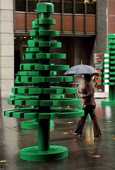 A woman walks through a life-sized LEGO forest during a wet morning in Sydney. AFP PHOTO / Greg WOOD.