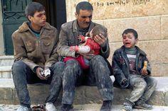 Ein Mann hält ein Baby im Arm, das nach dem Angriff auf den Ortsteil Masaken Hanano in Aleppo am 14. Februar aus dem Schutt gerettet werden konnte.