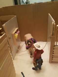 Model horse stable made from popciscle sticks and cardboard