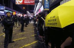 """HONGKONG-CHINA/ Police stand guard as a pro-democracy protester carries a yellow umbrella, symbol of the Occupy Central civil disobedience movement, while gathering with other protesters at Mong Kok shopping district in Hong Kong November 27, 2014. Two Hong Kong student leaders were banned from a large area in Mong Kok as a condition of bail on Thursday after they were arrested during scuffles as police cleared one of the largest protest sites that have choked the city for weeks. """"9.28""""…"""