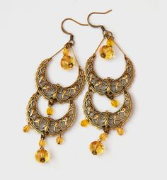 Delicate, beautiful antique brass crescent shaped filigree sprinkled with yellow Preciosa beads.        The perfect accessory for a night out!        Length: ~4 inches from top of the earwire