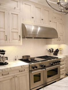 Nice revival of a kitchen in an early twentieth century house. The slight ware on the white cabinets coordinates nicely with the grains in the marble and stainless appliances. (pictures is the wolf 48 inch cooktop and ovens).
