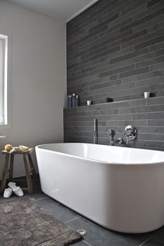 Hydro Systems pure white bathtub with silver hard wear and a grey tile wall flowing down to the floor. Clean and contemporary.