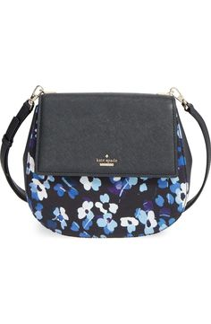 A squared-off flap in textured leather adds a smart edge to this rounded crossbody bag by Kate Spade featuring a lighthearted floral print. A full-length exterior pocket, spacious interior and optional, adjustable crossbody strap add convenience to the engaging style.