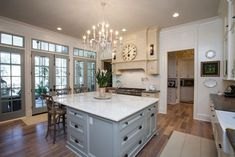 This roomy kitchen is a vision with white oak floors, an oversized Calcutta Gold marble island, limestone countertops and an elegant chandelier for a splash of sparkle. French doors lead to the courtyard for open-air living.