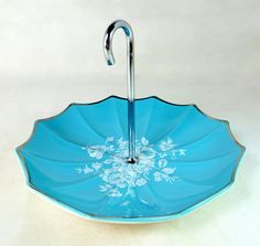 This is a sweet vintage cake plate made by the Midwinter pottery in England and produced in the mid century modern era, with a production date of October 1960.  The dish has the distinctive ribbed umbrella shape used by Midwinter as part of their Stylecraft range, with the curved chrome metal handle shaped like an umbrella handle. It is decorated in a light blue turquoise or aqua colour, and has a finely detailed pattern of flowers and leaves in the centre in white. It is a perfect dish for…