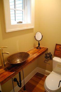 Tampo em linha de madeira com cuba pequena de sobrepor, sem armário inferior. Observar tipo de piso e rodapés utilizados.