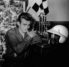 James Dean posing with his racing gear and trophies.