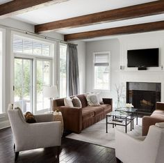 Stunning ceiling beams bring warmth and texture to this gray living room.| Summit Signature Homes, Inc.