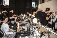Sheer chaos: Models sit on stools as make-up artists and hair stylists crowd…