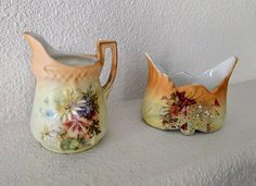 Vintage creamer and sugar set, ca. 1910s. Unsigned, but numbers are stamped on the bottoms. Creamer: 4 3/4 tall x 3 1/2 diameter at the base  Sugar Bowl: 3 3/4 tall x 5 wide x 3 deep  Painted porcelain with wildflower bouquet motif, metallic gold rim, and decorative shapes. Autumnal tones of peach, muted orange, pale green, maroon, olive green, soft blue, and white.  Matte glazed exterior finish, glossy white interior finish.   Good vintage condition. No chips or cracks. The go...