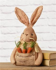 "Create a spring vignette on your mantel or a shelf with this stuffed fabric bunny doll, featuring a trio of carrots tucked in a burlap pocket that reads ""carrot collector."" Accented with cheesecloth, buttons, and beads. Bunny Crafts, Easter Crafts, Crafts For Kids, Diy Crafts, Primitive Carrots, Easter Parade, Spring Crafts, Easter Bunny, Bunny Rabbit"