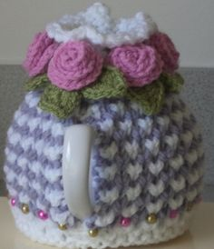 knitted to my own design in pretty bee stitch with a stocking stitch fluted and picot top, this wee tea cosy is in doubled double knitting in white and a very pretty shade of soft lavender which looks almost grey..........  the meadow green crochet cord threads through the top of the cosy and wraps around ....  i knitted 5 rolled roses in a very soft dusky pink yarn with meadow green leaves and these are sewn to the ends of the cord and to the top of the cosy....  i have carefully sewn have…