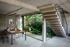 Nestled in the urban city of Sao Paulo, Brazil, Maracanã House is a breath of fresh air designed by architecture studio Terra e Tuma Arquitetos Associados. Industrial Home Design, Industrial House, Modern Industrial, Industrial Basement, Concrete Stairs, Concrete Floors, Concrete Bricks, Metal Stairs, Exposed Concrete